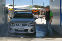 hosing down car in self serve smiley car wash